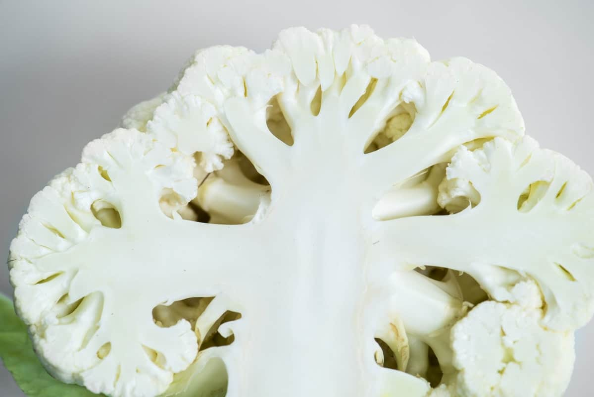 cauliflower cut in half to show stem, leaves, and florets