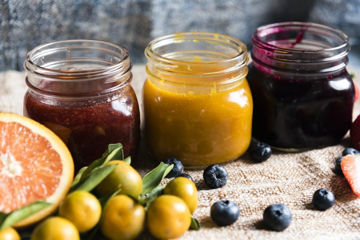 homemade jam in three jars with fruits surrounding it